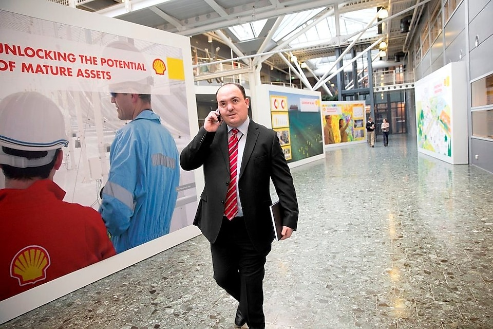 Andy Kneen walking and talking on the phone at a Shell office