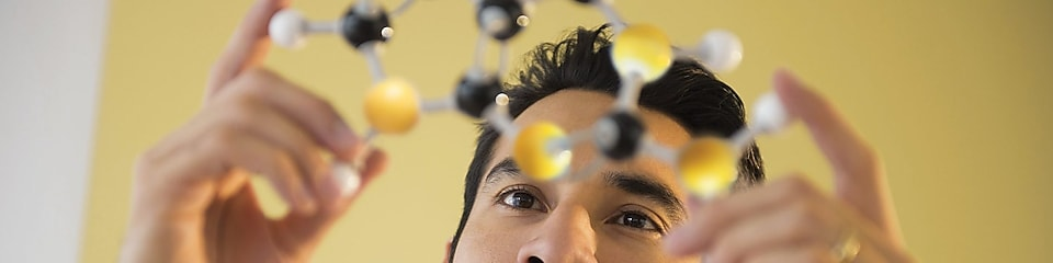 Young man examining molecular model