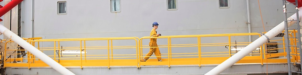 Engineer walking across a North sea offshore platform in Aberdeen