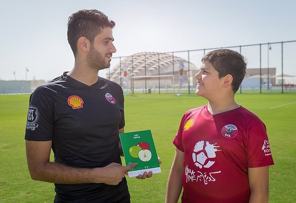 QFA coaching member giving training to football player