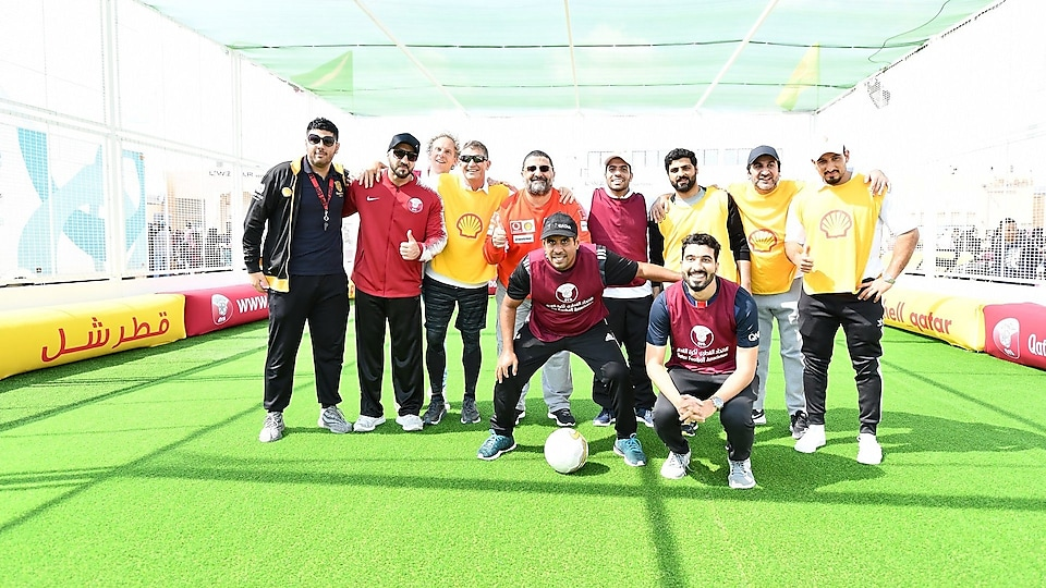 Management teams of Qatar Football Association and Qatar Shell participate in a football game.