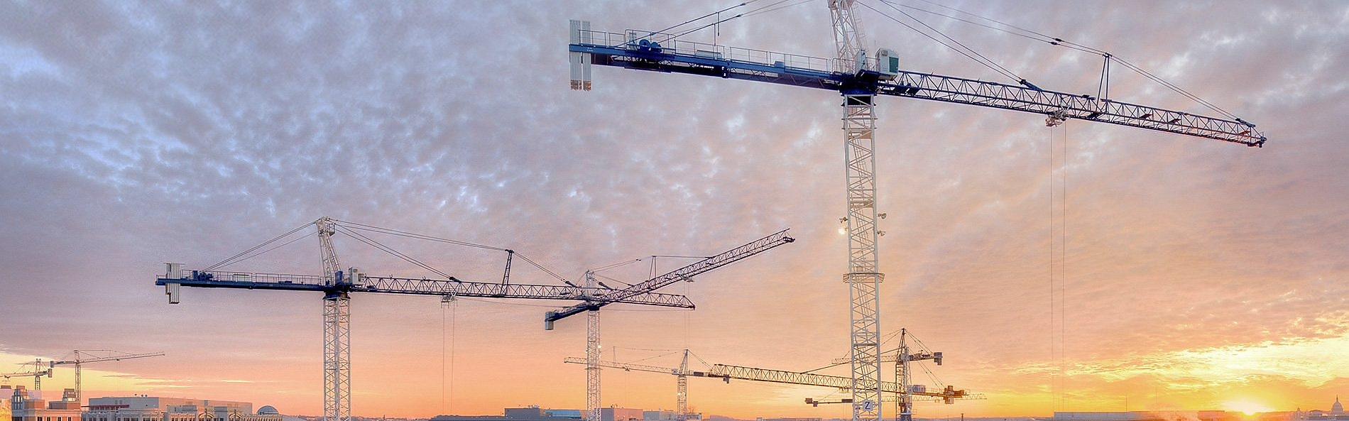 three cranes on a building site at dusk